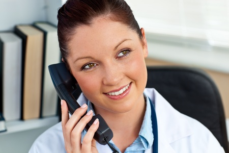 Attractive female doctor phoning in her office photo
