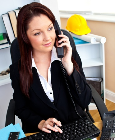 Confident businesswoman talking on phone using her computer photo