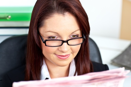 Delighted young businesswoman reading a newspaper Stock Photo - 10249737