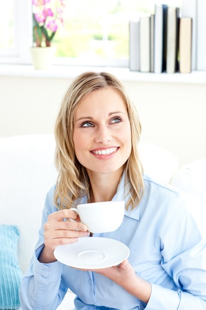 Captivating businesswoman holding a cup sitting on a sofa photo