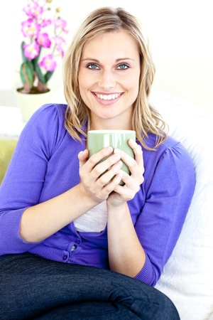 Caucasian blond woman enjoying her coffee sitting on the sofa in the living-room photo