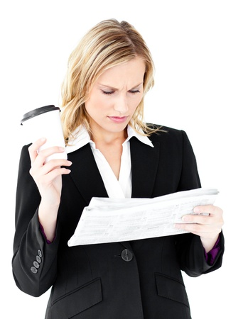 Attractive businesswoman reading a newspaper holding a coffee Stock Photo - 10241367