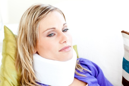 Beautiful woman wearing neckbrace lying on a sofa photo