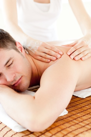 Positive caucasian man having a back massage in a spa center photo