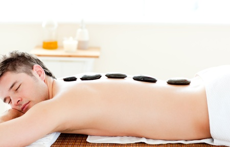 Relaxed man having with hot stone on his back  photo
