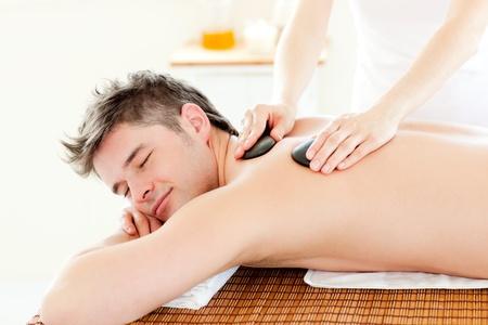 Charming man enjoying a massage with hot stones photo