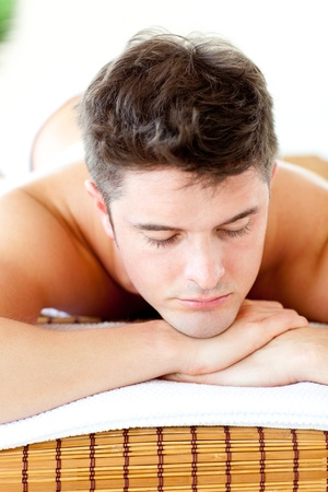 Caucasian relaxed young man lying on a massage table  photo