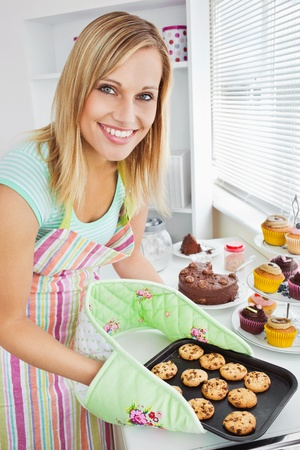 home baking: Smiling woman holding cookies in the kitchen