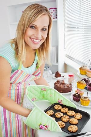 Lachende vrouw die koekjes in de keuken
