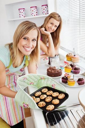 Lyckliga kvinnliga vänner som håller kakor i köket Stockfoto