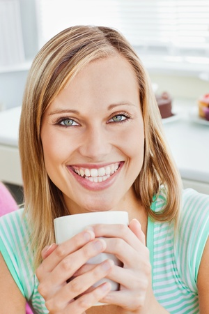 Glowing woman holding a cup of coffee at home photo