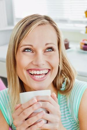 Lachende Frau h�lt eine Tasse Kaffee zu Hause