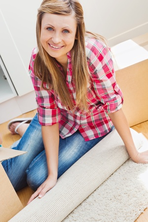Smiling woman unpacking a box on the floor photo