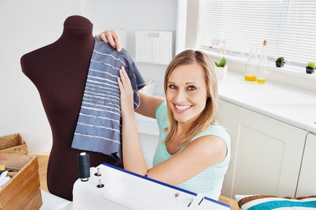 Merry woman sewing clothes at home  photo