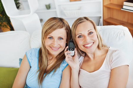 Two smiling women using a cellphone at home photo