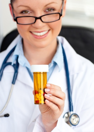 Glowing young female doctor holding pills photo