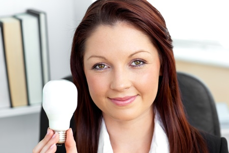 Confident young businesswoman holding a light bulb looking at the camera photo