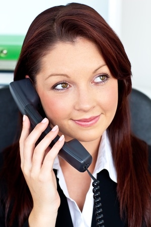 Pretty businesswoman talking on phone sitting photo