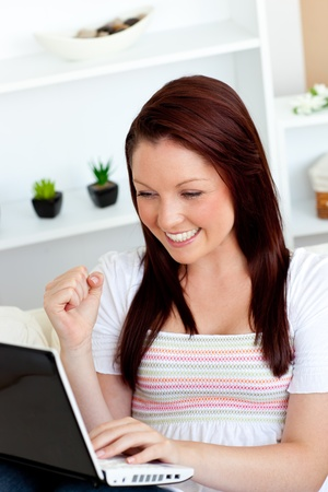 Joyful young woman using her laptop sitting on a sofa Stock Photo - 10242064