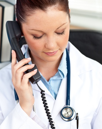 serious doctor: Portrait of a serious female doctor phoning in her office Stock Photo