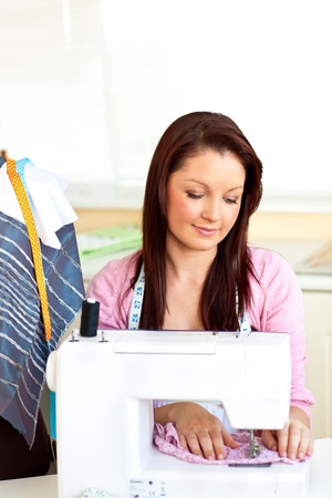Concentrated caucasian woman sewing at home photo