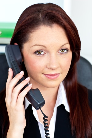 Positive businesswoman phoning in her office photo