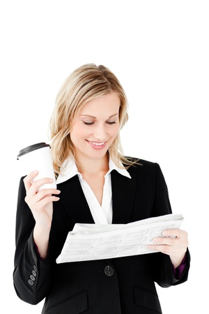 Beautiful businesswoman holding a cup of coffee reading a newspaper Stock Photo - 10241365