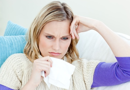 Diseased woman lying on a sofa with tissues