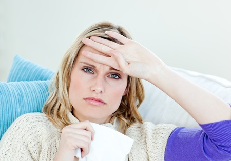 feeble: Diseased woman lying on a sofa with tissues and feeling her temperature