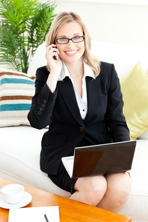 Elegant businesswoman using her phone and laptop in her living-room photo