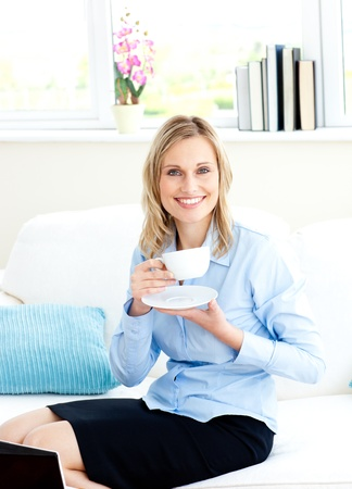 Smiling businesswoman drinking coffee sitting on a sofa photo