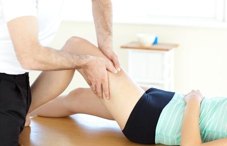 masaje deportivo: Joven terapeuta f�sico dando un masaje en las piernas