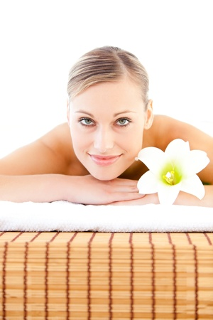 Close-up of a radiant woman lying on a massage table with a flower photo