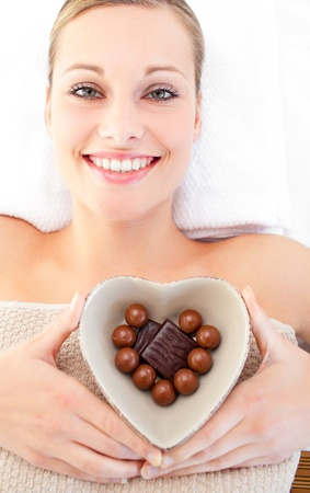 Cheerful woman holding a bowl in the shape of a heart with chocolate photo