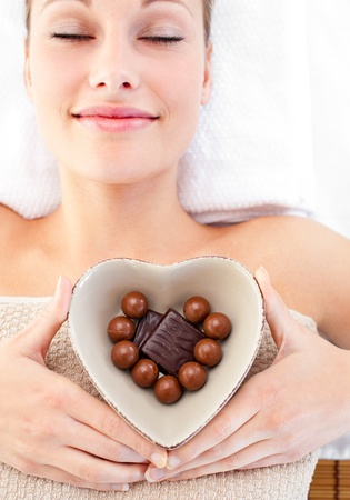 woman in towel: Bright woman holding a bowl in the shape of a heart with chocolate