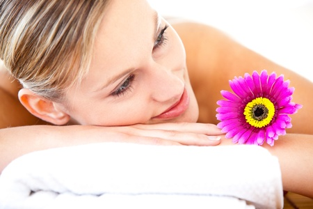 Close-up of a bright woman lying on a massage table with a flower photo