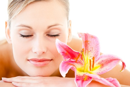Close-up of a pretty woman lying on a massage table with a flower