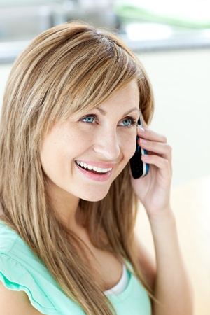 gratified: Cheerful woman answering the phone in the kitchen