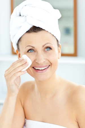 Smiling young woman with a towel putting cream on her face in the bathroom Stock Photo - 10241446