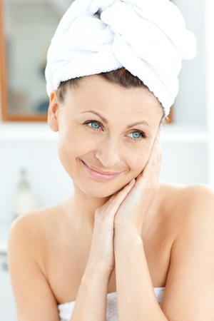 Radiant young woman with a towel putting cream on her face in the bathroom Stock Photo - 10242745