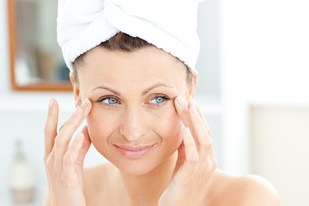 Attractive young woman with a towel putting cream on her face in the bathroom Stock Photo - 10241361