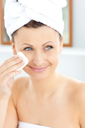 Pretty young woman with a towel putting cream on her face in the bathroom Stock Photo - 10241476
