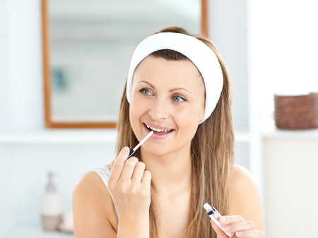 Happy woman applying gloss on her lips in the bathroom Stock Photo - 10241377