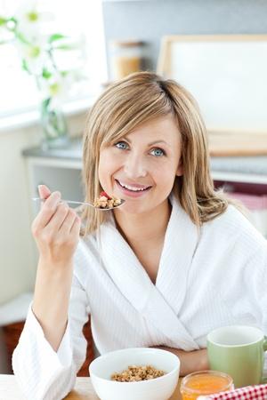 Cute woman having breakfast in the kitchen photo
