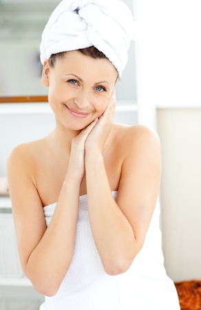 Attractive young woman with a towel putting cream on her face in the bathroom Stock Photo - 10241169