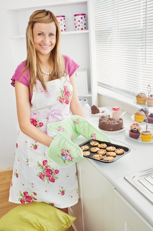 Positive young woman baking cookies in the kitchen photo