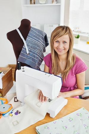 Positive young woman sewing clothes at home photo