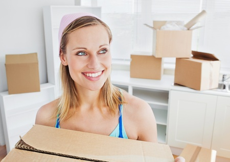 home moving: Positive woman carrying boxes at home