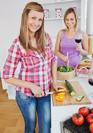 Two smiling women cooking together at home photo