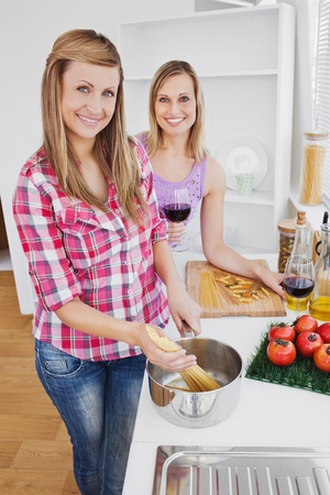 domestics: Radiant women cooking spaghetti together in the kitchen Stock Photo